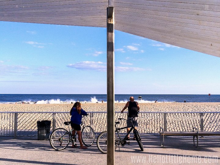 Two people with bikes looking at the ocean from the boardwalk.
