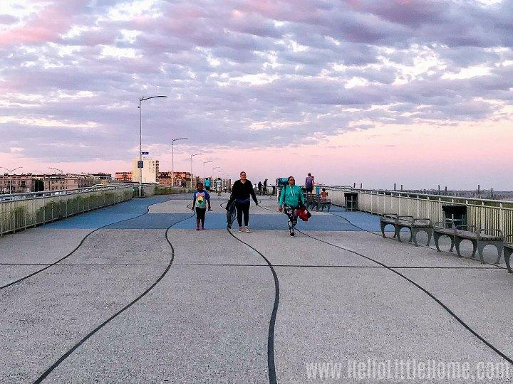 People walking on the Rockaway Beach Boardwalk at sunset.