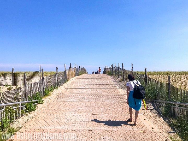 A woman walking onto Rockaway Beach in NYC.