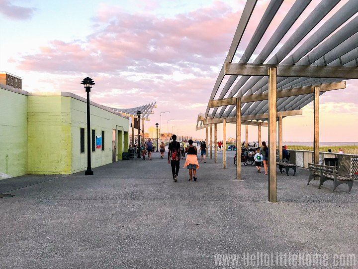 People walking on the boardwalk near a restaurant at sunset.