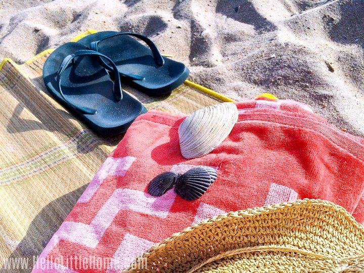 Flip flops, a beach towel, and sea shells on a beach mat.