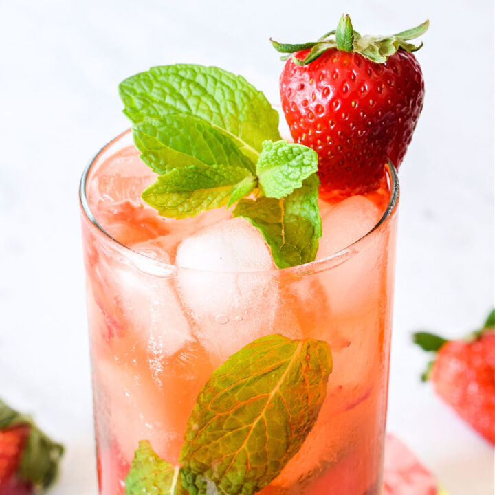 Closeup of the finished fresh Strawberry Mojito garnished with mint and a berry.