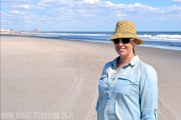 On woman wearing a hat and blue shirt standing on the beach.