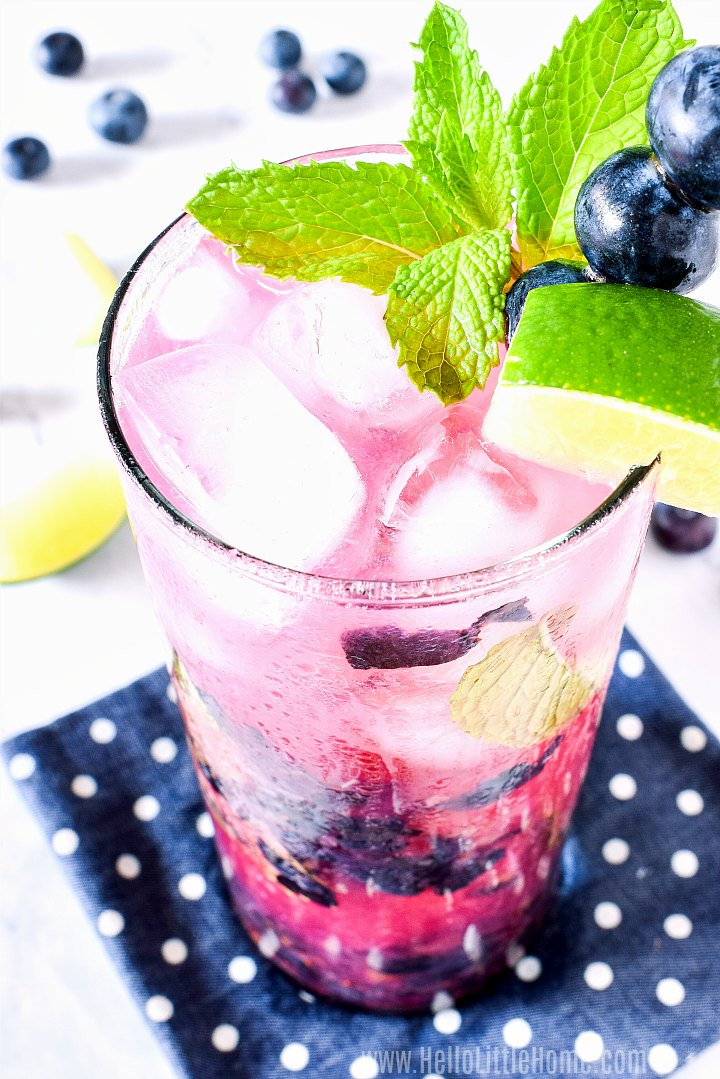 A Blueberry Mint Mojito on a polka dot napkin on a white marble counter.