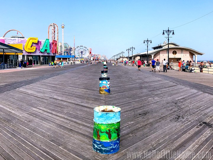 The Coney Island Boardwalk with amusement park on one side and beach on the other.