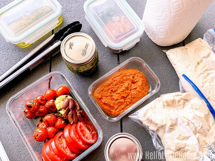 Grilled pizza ingredients - dough, cheese, veggies, and sauce - on a table.