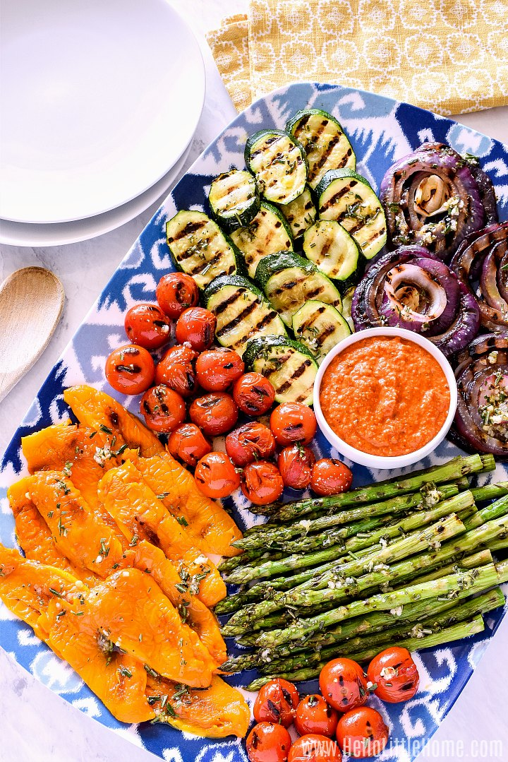 A platter of grilled vegetables, white plates and yellow napkins on a marble counter.