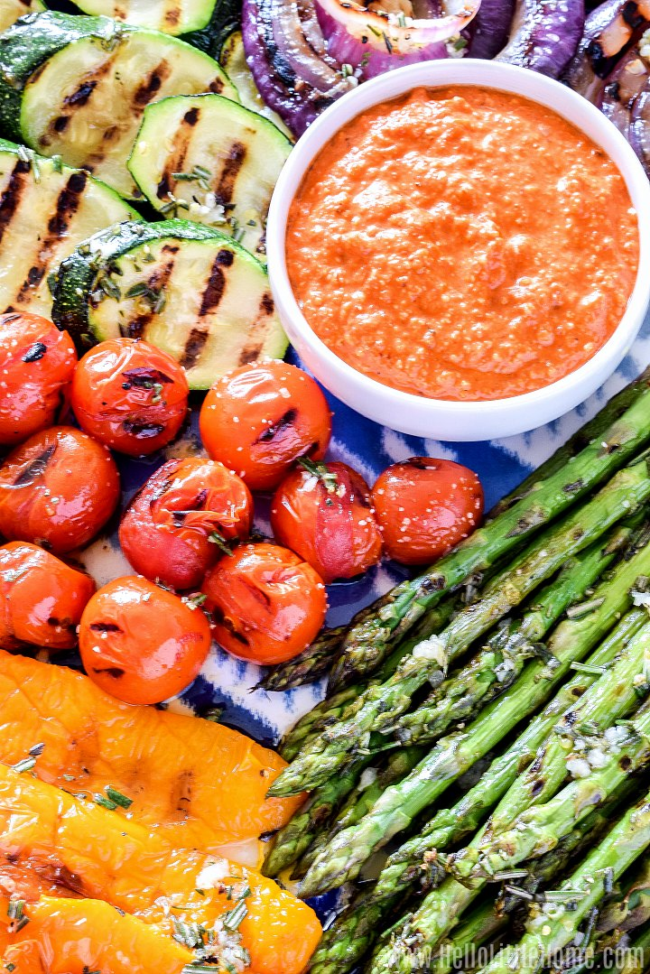 A platter of grilled veggies with romesco sauce.