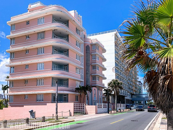 A pink art deco building on a street in Condado.