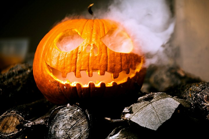 A jack-o-lantern with smoke coming out of it at a Halloween party.