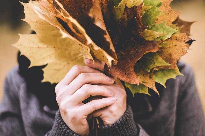 A woman holding leaves in front of her face.