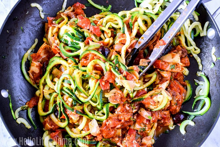 Using a pair of tongs to mix zucchini spaghetti with sauce.
