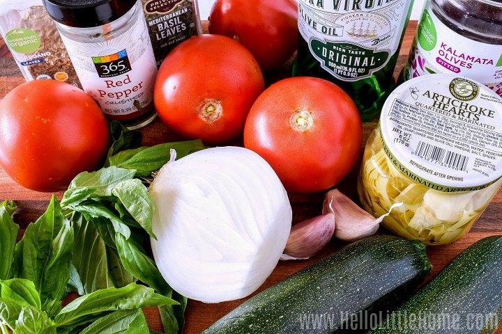 Zucchini spaghetti ingredients: tomatoes, artichokes, onion, spices, and zucchini.