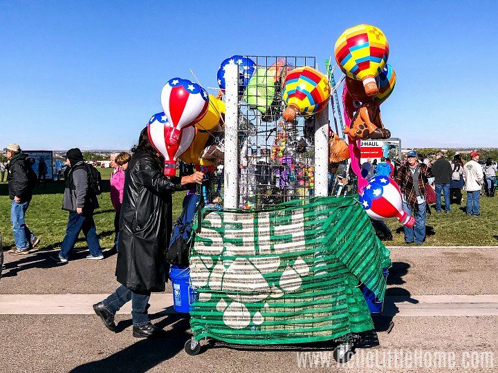 A vendor pushing a cart with Balloon Fiesta souvenirs.