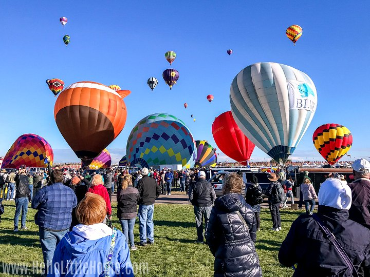 Multiple balloons launching and filling the sky at the Albuquerque Balloon Festival.