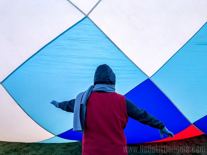 A crew member blocking the crowd from touching an inflating balloon.