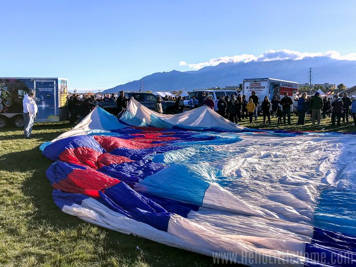 A crew laying out their hot air balloon on the field.