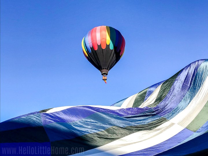 A colorful hot air balloon floating over an inflating balloon.