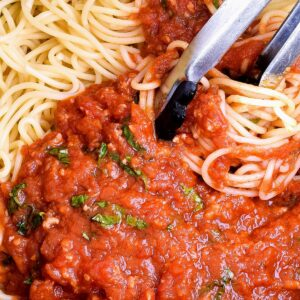Mixing Marinara Sauce and Spaghetti with tongs.
