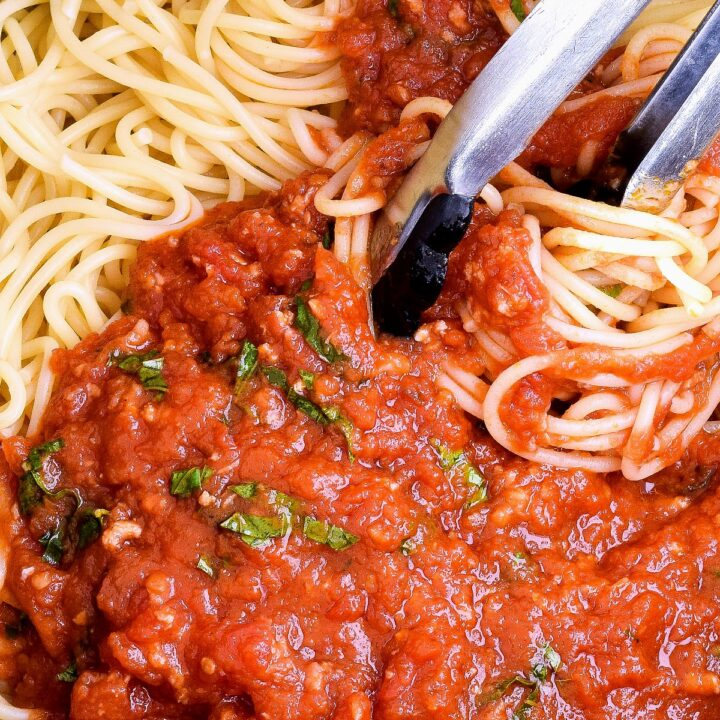 Mixing Marinara Sauce and Spaghetti with tongs.