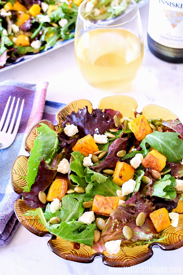 A bowl of Pumpkin and Feta Salad with a platter of salad and wine glass in the background.