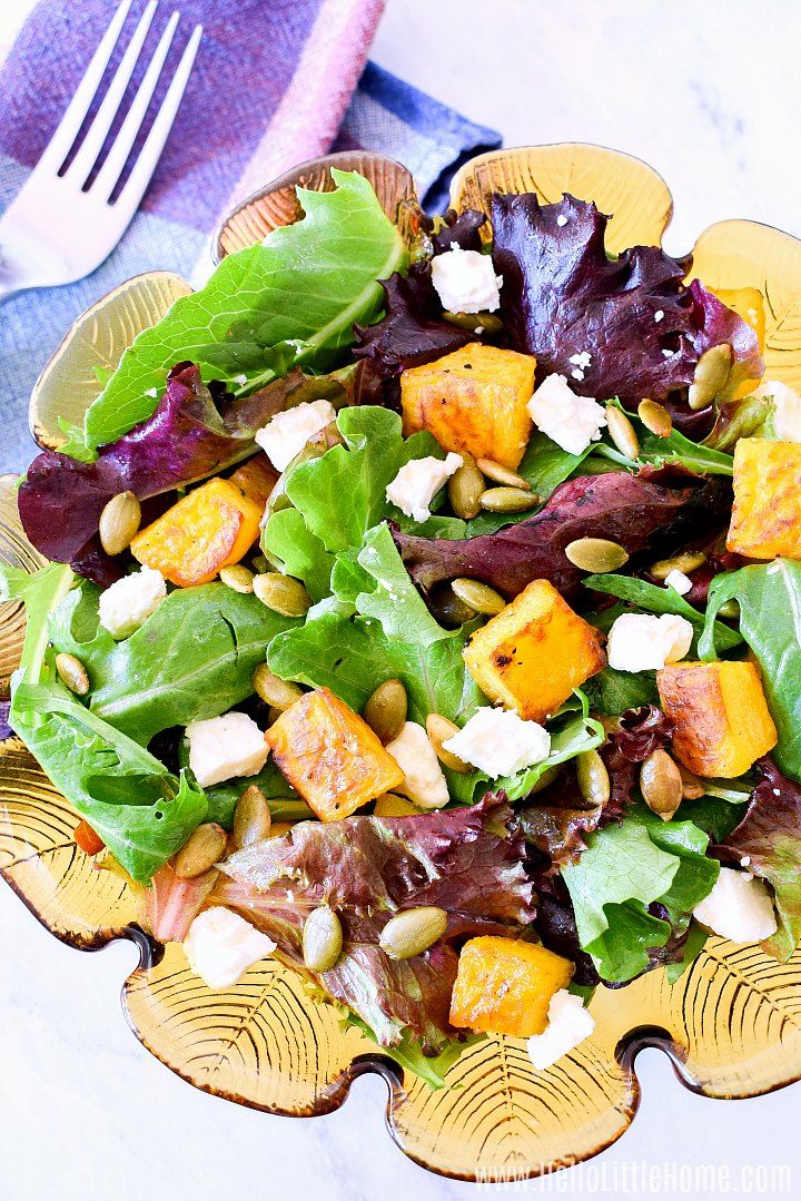 A bowl of Pumpkin Salad topped with Feta Cheese and Pepitas.