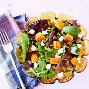 A Roasted Pumpkin Salad with Feta and Maple Dressing on a white marble counter.