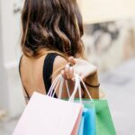 A woman holding colorful shopping bags during Black Friday + Cyber Monday Sales.