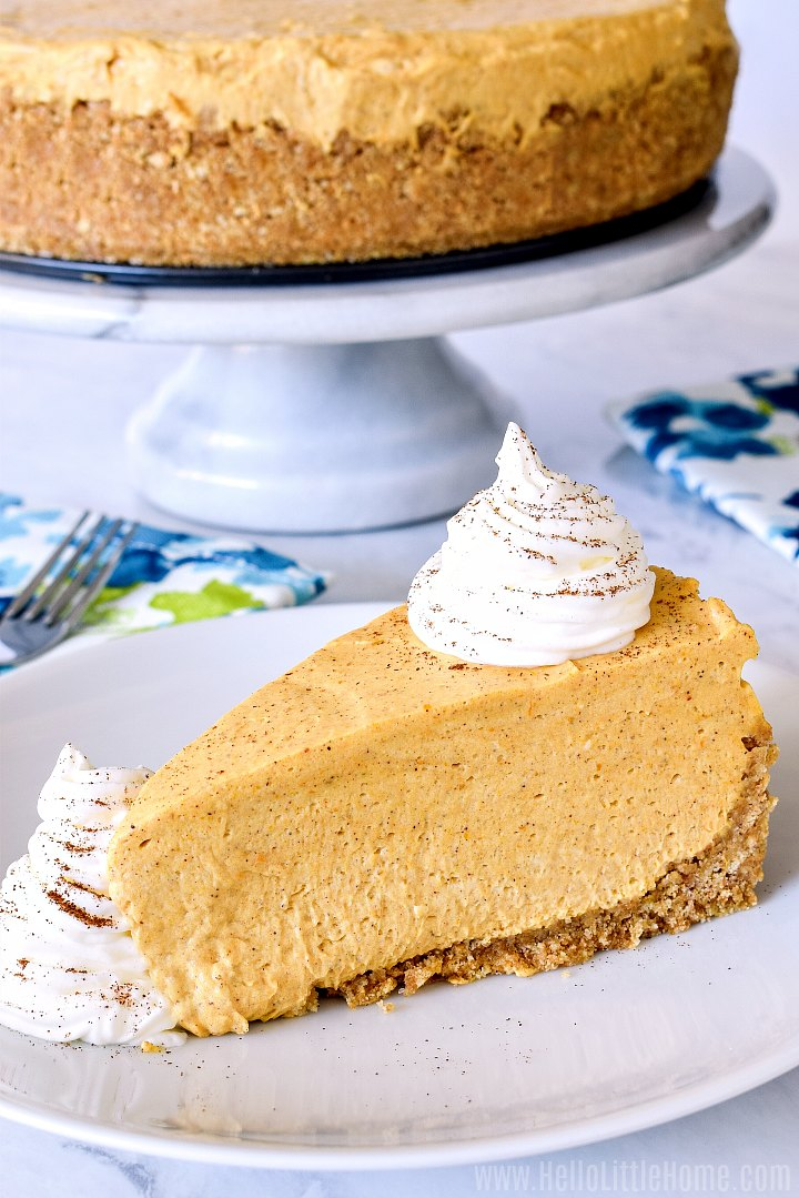 A slice of pumpkin cheesecake with the whole cheesecake in the background.