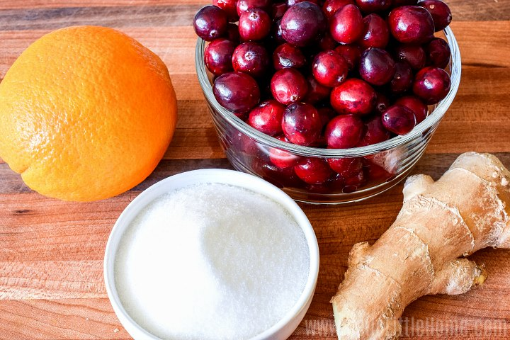 Ingredients for homemade cranberry sauce with orange juice and orange zest on a wood cutting board.