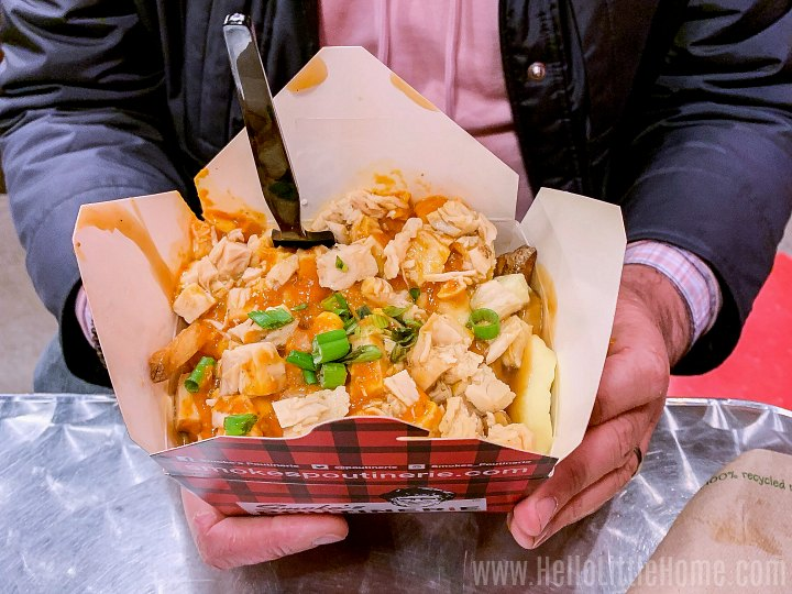 Hands holding a box of poutine from Smoke's Poutinerie.