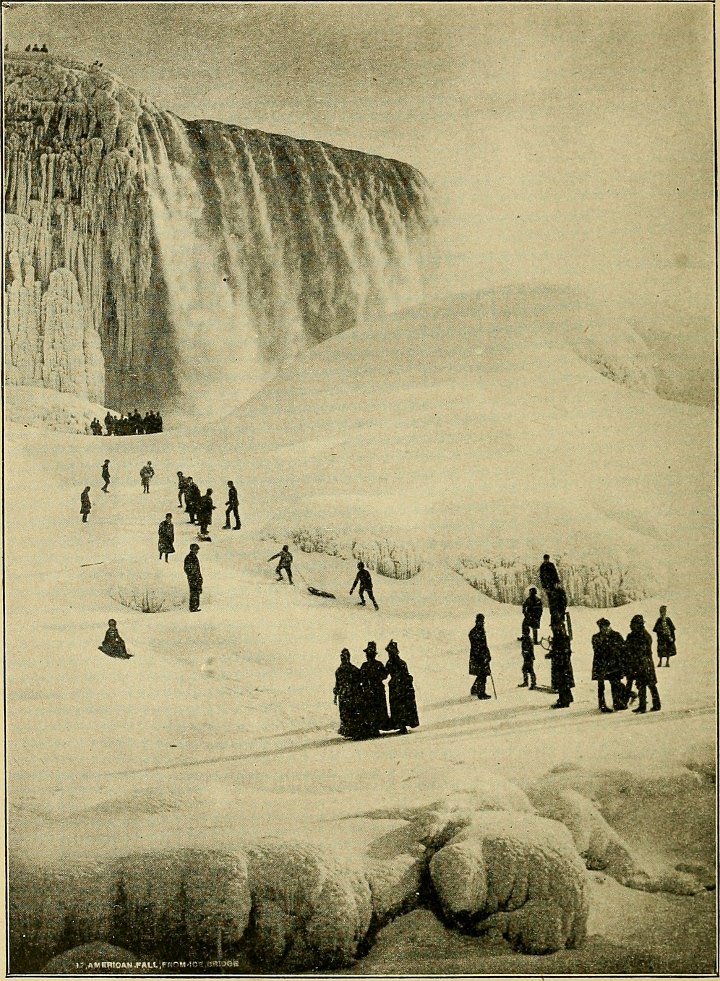 A vintage photo of people walking on the ice below Niagara Falls.