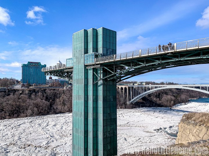 People walking on the Niagara Falls Observation Tower with the icy river below them.