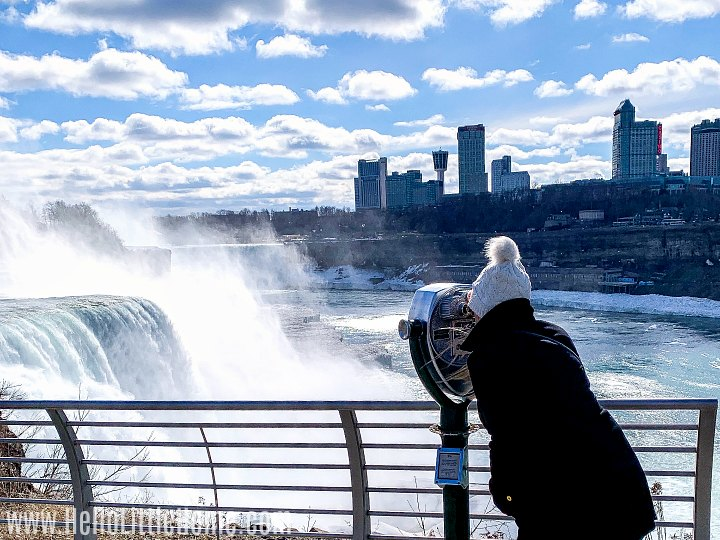 A woman looking at the falls through a telescope.