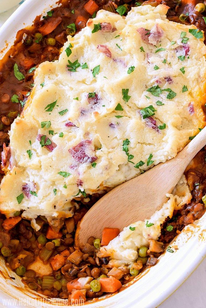 A wood spoon in a pan of vegetable lentil Shepherd's Pie.