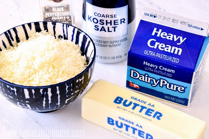 Recipe ingredients (Parmesan, butter, heavy cream, and salt and pepper) arranged on a marble counter.