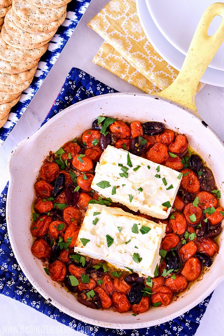 A yellow skillet with Baked Feta with Tomatoes and Olives served with crackers.