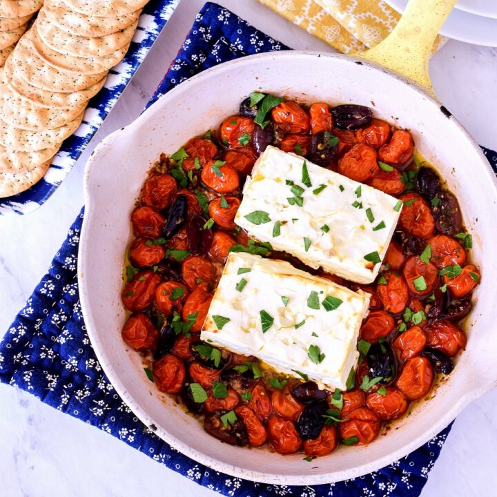 Baked Feta in a yellow skillet on a blue pot holder.