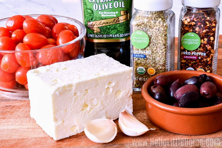 Baked Feta Cheese ingredients: grape tomatoes, feta, garlic, olives, olive oil, and spices.