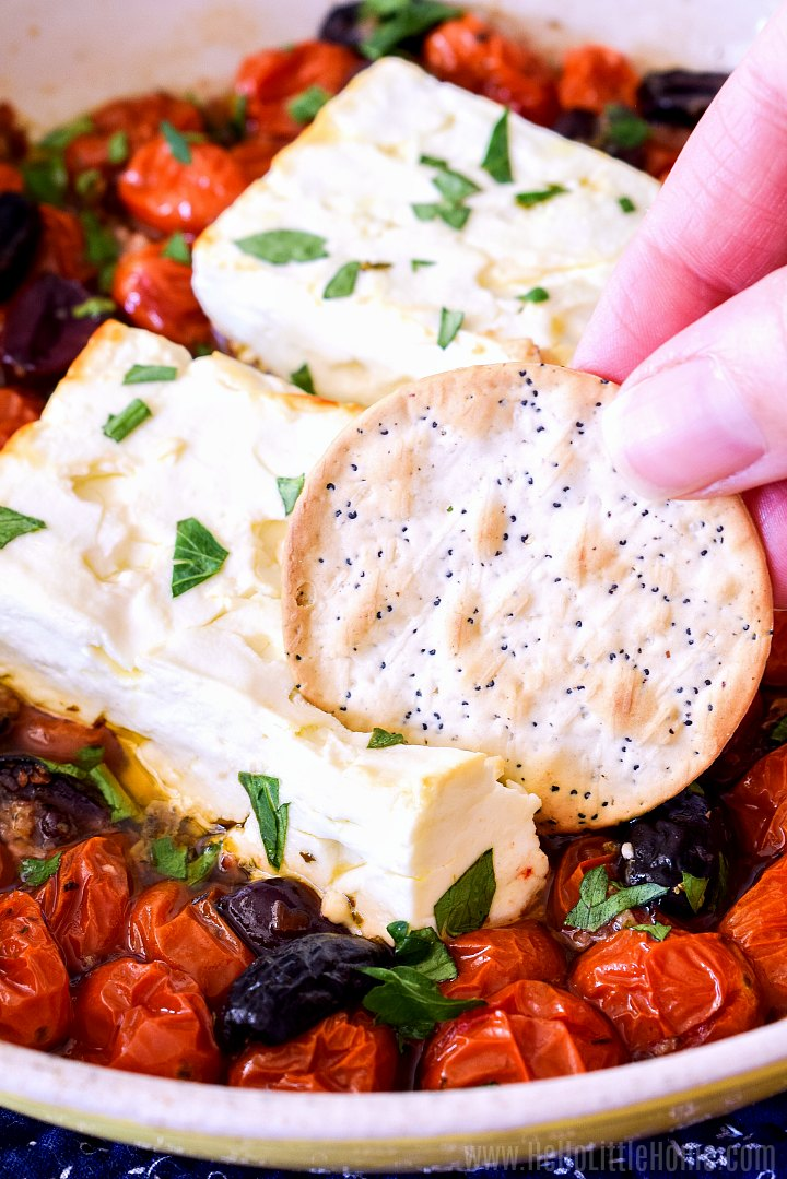 A hand sticking a cracker in Baked Feta Dip.