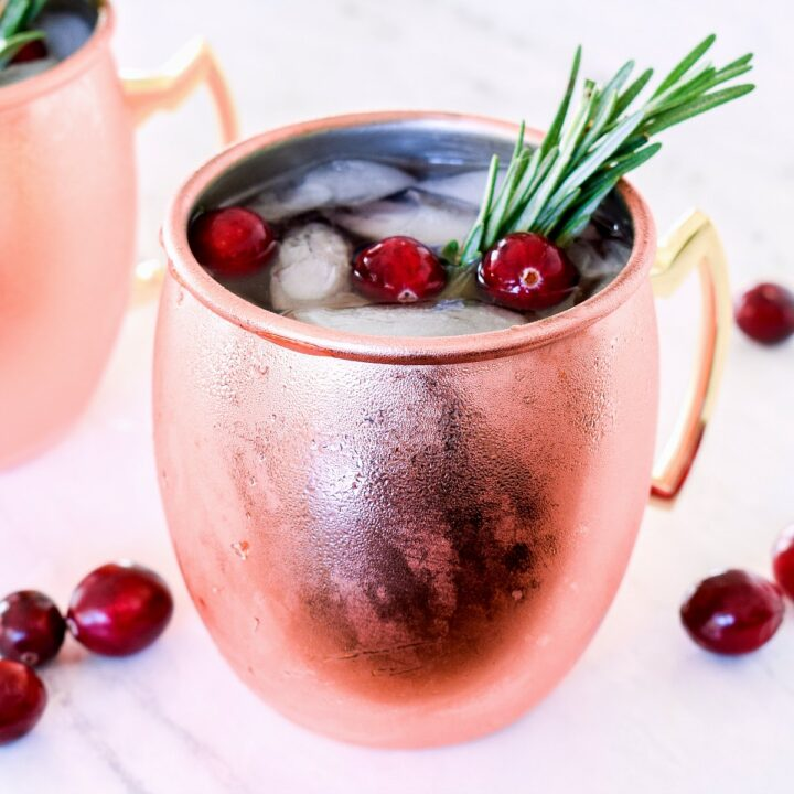 A Cranberry Moscow Mule served in a copper mug and garnished with rosemary.