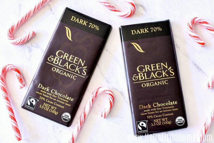 Dark Chocolate Bark ingredients on a white marble counter: chocolate and candy canes.