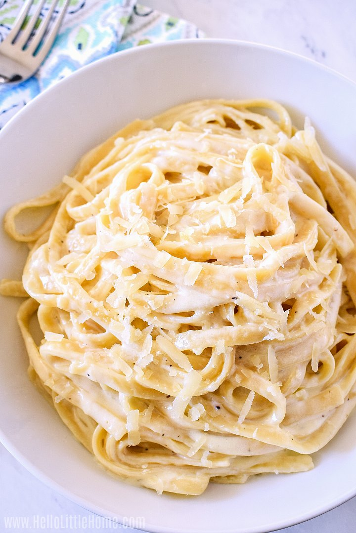 A big bowl of Pasta Alfredo sprinkled with Parmesan cheese.