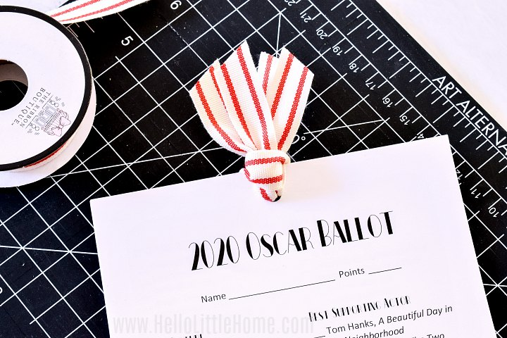 A 2020 Oscar Ballot printable tied together with ribbon on a black cutting mat.