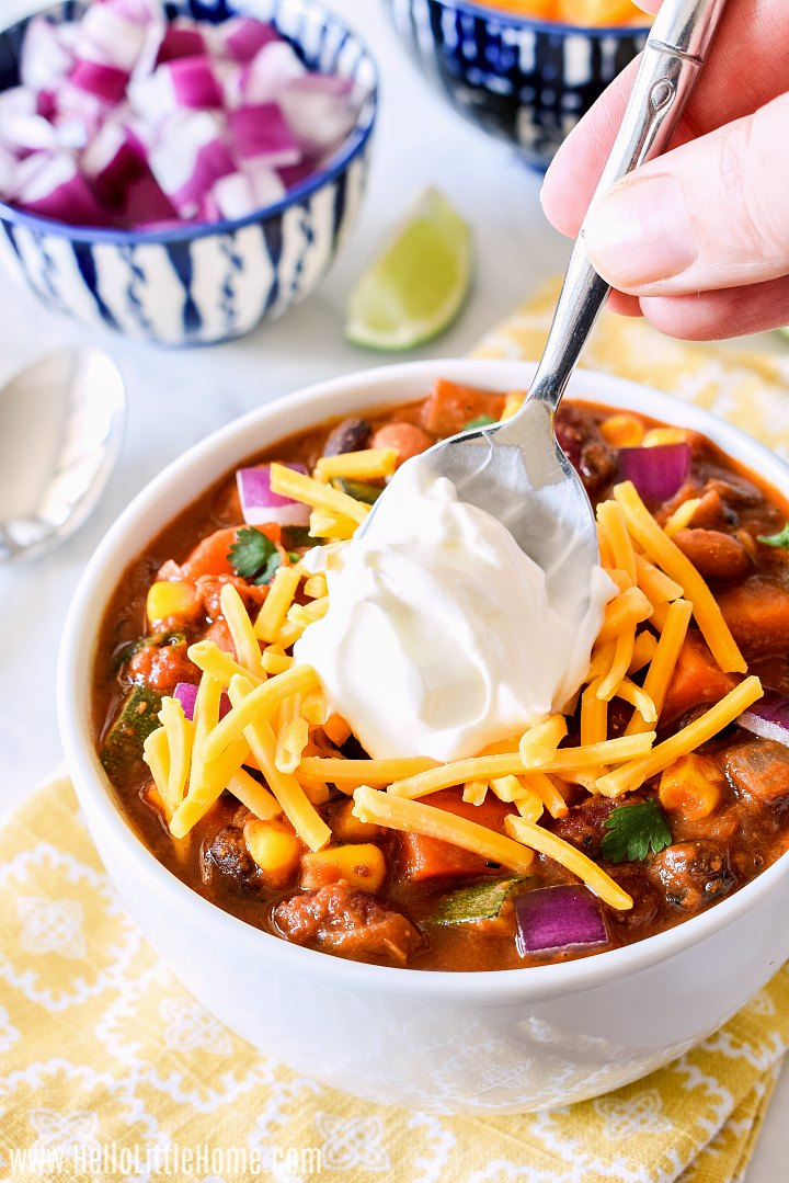 A hand adding a spoonful of sour cream to a bowl of bean chili.