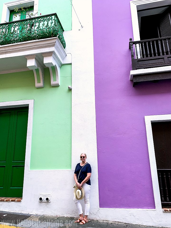 A woman standing in between green and purple buildings in Old San Juan.