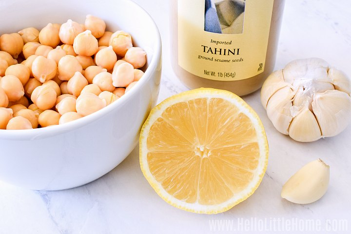 Recipe ingredients (chickpeas, tahini, lemon, and garlic) on a marble counter.