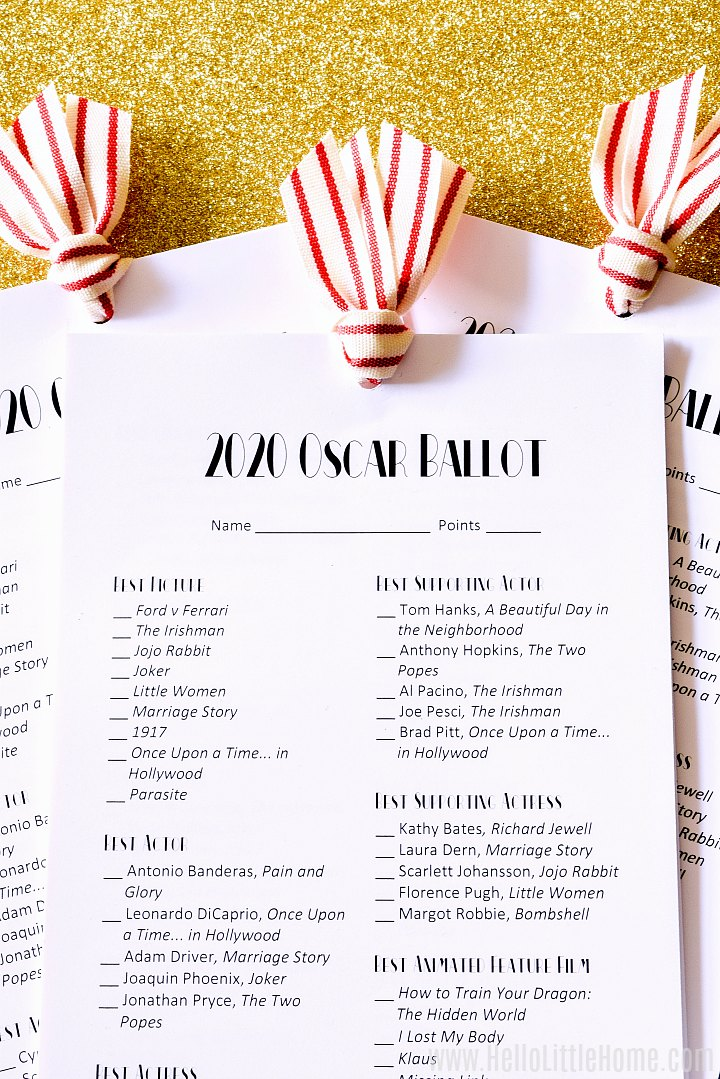 Three Oscar Ballot 2020 Printables tied together with striped ribbon on a gold glitter background.