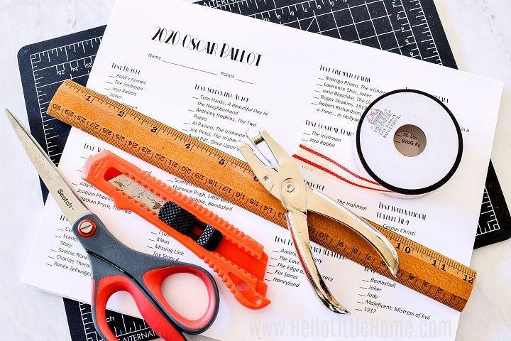 Supplies for assembling the Oscar Ballot printable: scissors, cutting mat, ruler, ribbon, hole punch.