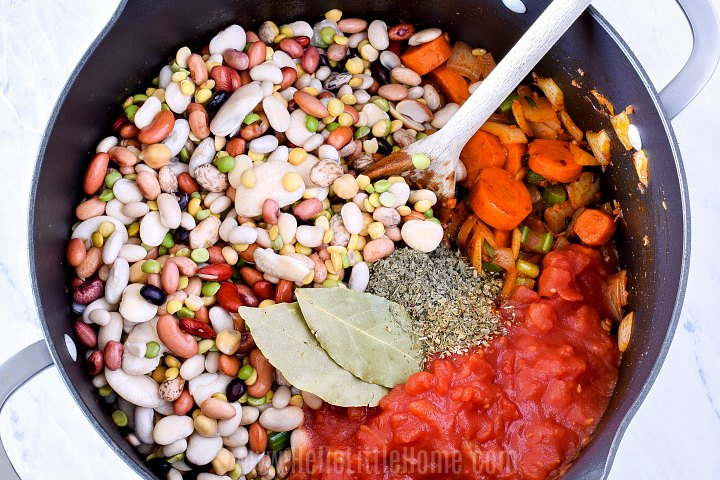 Stirring 15 bean mix, tomatoes, and spices into soup.